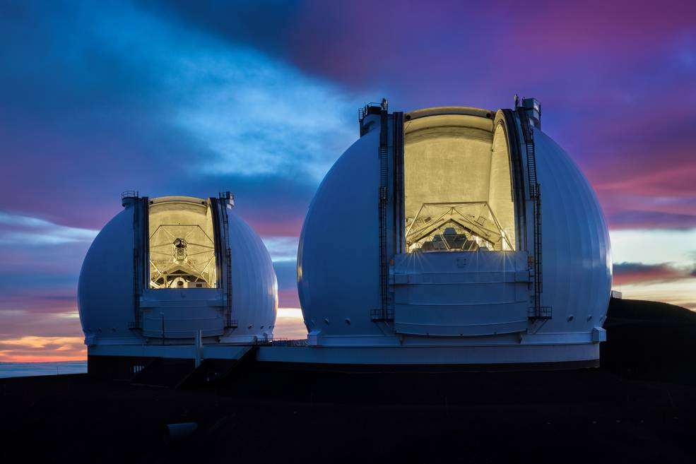 Image of light from two large telescopes pouring out onto a pink, sunset sky