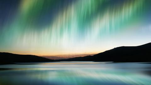 A blue and green aurora appearing over a body of water and a mountain range in the background