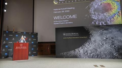 Man stands at podium next to two screens with text and images of the Moon