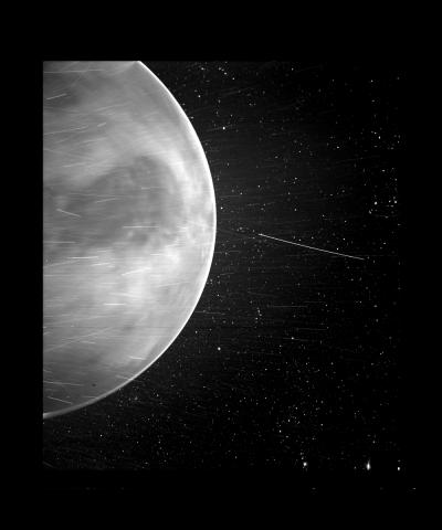 Black-and-white image of Venus with stars and streaks of light crossing in front of it