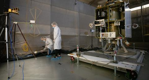 Two people in white coats and hairnets stand over a piece of spacecraft in a dark room