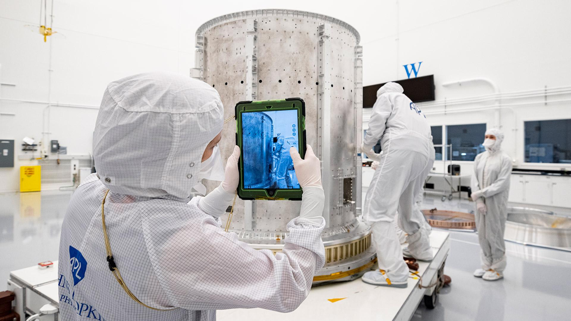 Three APL engineers in white clean room suits, one taking a photo with an iPad of another working on a large metal tank