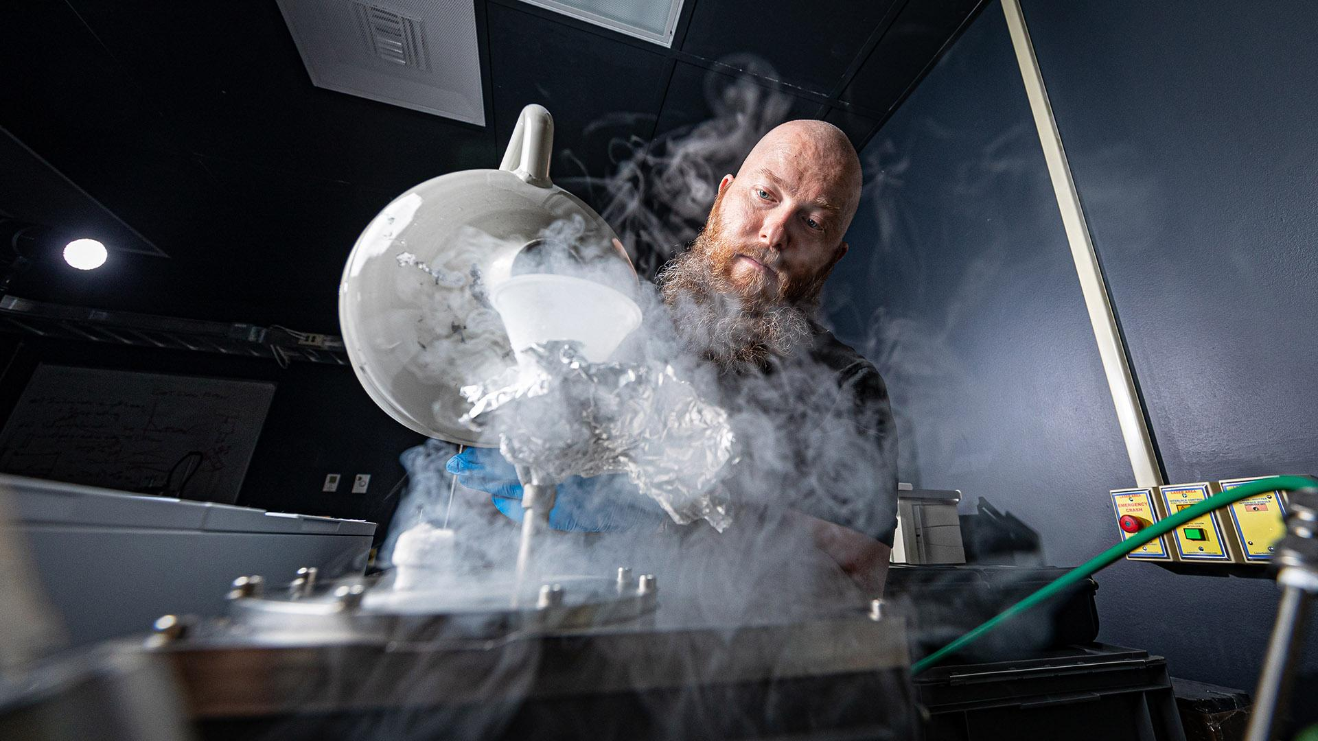 APL staff member pouring liquid nitrogen into a funnel