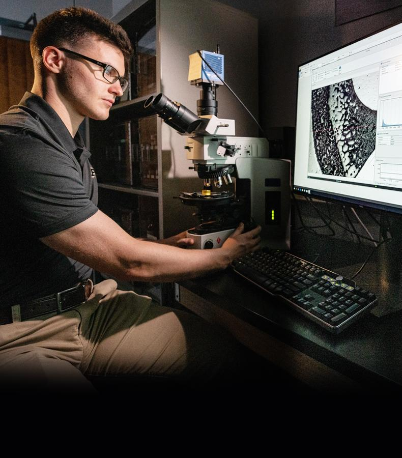 Image of APL Scientist Looking at Microscopic Image.